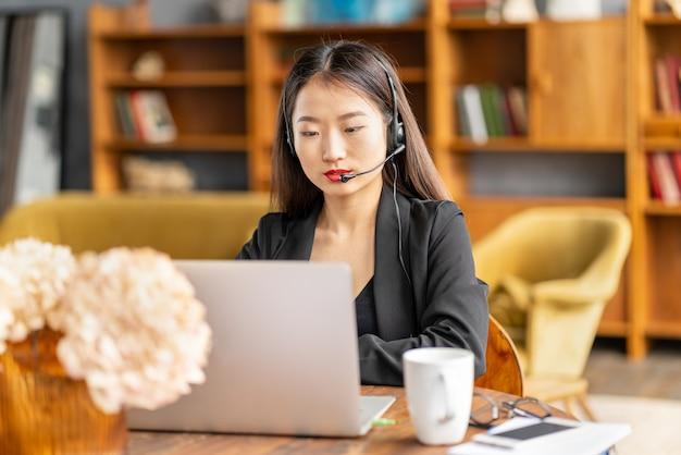 Азиатская деловая женщина в гарнитуре разговаривает по конференц-связи и видеочату на ноутбуке в офисе Premium Фотографии