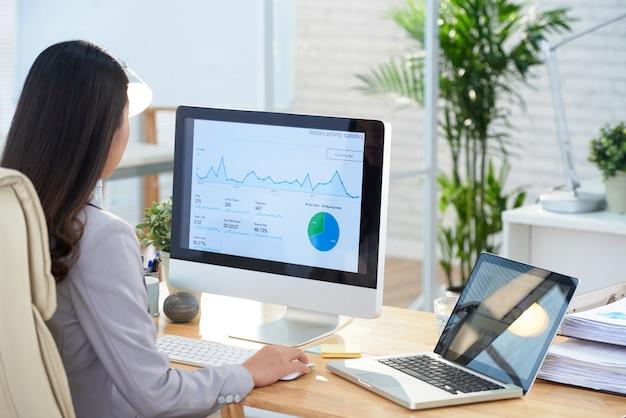 Donna di affari asiatica che si siede allo scrittorio in ufficio e che studia i grafici sullo schermo di grande computer Foto Gratuite