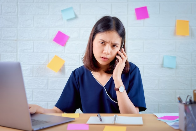 Asian businesswoman using smartphone with feeling strain from hard work for a long time in the desk office room. Premium Photo
