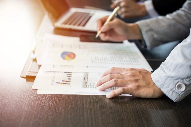 Азиатские коммерсантки держа ручку и документы анализа на таблице офиса с работой диаграммы портативного компьютера и диаграммы финансовой Premium Фотографии