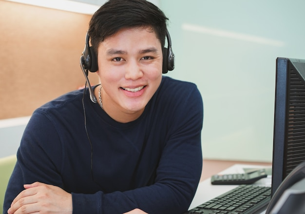 Asian call centre man with headset at desktop office Premium Photo