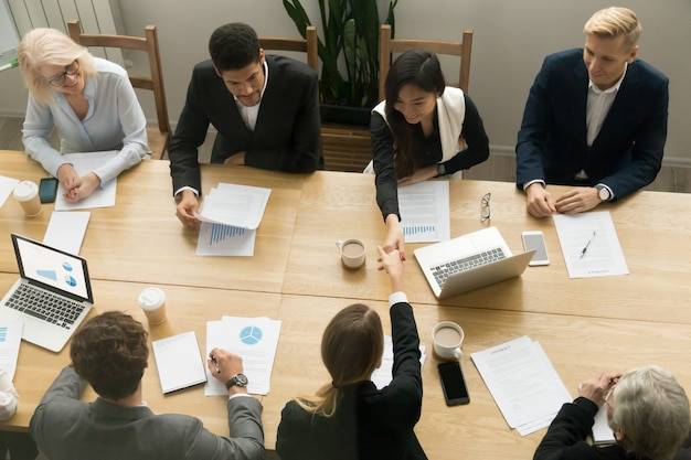 Asian and caucasian businesswomen handshaking at group meeting, top view Free Photo