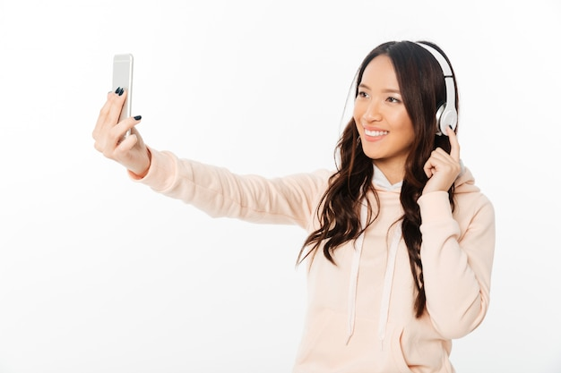 Asian cheerful woman listening music make selfie by mobile phone. Free Photo