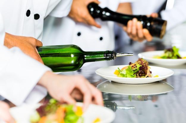 Asian chef in restaurant kitchen cooking Premium Photo