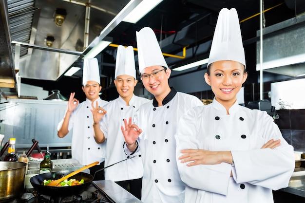 Asian chefs in hotel restaurant kitchen Premium Photo