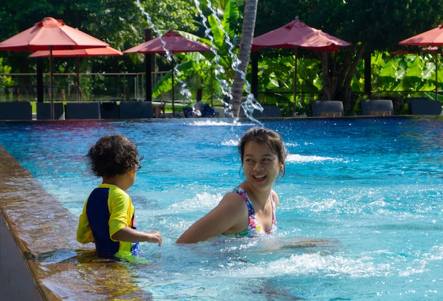 Asian child boy learn swimming in a swimming pool with mom Premium Photo