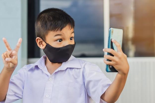 Covid-19病とコロナウイルスを防ぐために彼の顔に黒い布のマスクを身に着けているアジアの子供男の子。 Premium写真