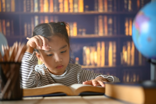 Asian child  girl  industrious  is sitting at a desk  indoors. kid is learning in home Premium Photo