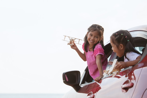 Asian child girl playing with toy wooden airplane with her sister while travel by car Premium Photo