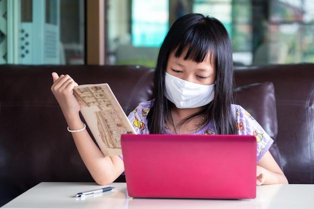 Азиатская девушка ребенка изучая домашнюю работу и нося лицевой щиток гермошлема во время ее онлайн урока дома для защищает вирус 2019-ncov или covid 19, онлайн концепцию образования. Premium Фотографии