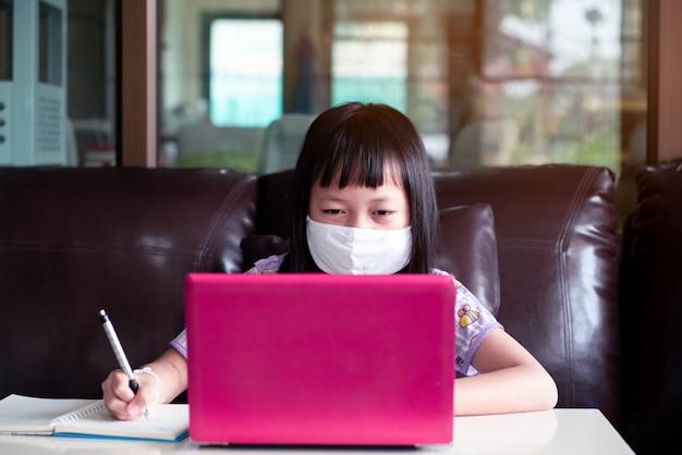 Азиатская девочка, изучающая домашнюю работу и носящая маску для лица во время онлайн-урока дома для защиты от вирусов 2019-ncov или covid 19 Premium Фотографии