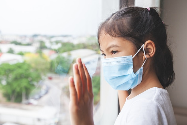 Premium Photo   Asian child girl wearing protection mask looking outside  through the window and stay at home
