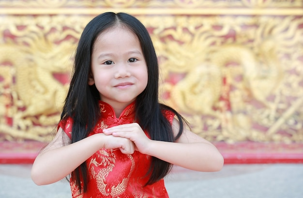 Asian child girl wearing red cheongsam with greeting gesture celebration Premium Photo