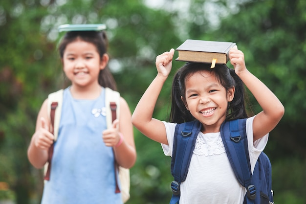 Asian child girl with school bag and her sister put a book on head together Premium Photo
