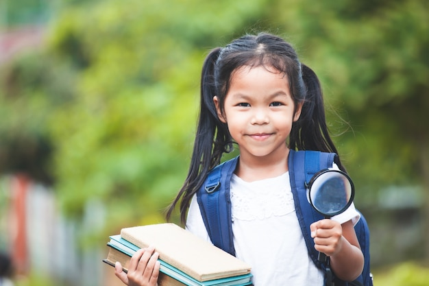 Asian child girl with school bag holding books and magnifying glass ready to go to school Premium Photo
