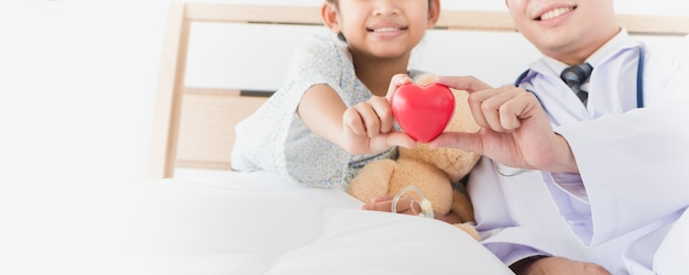Asian child's hand and male doctor hold red heart lying on bed in the hospital. Premium Photo
