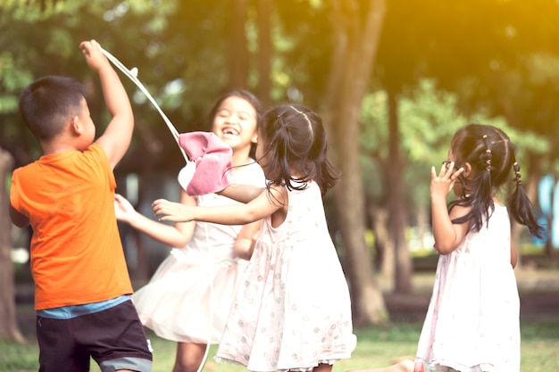 Asian children having fun to play together in the park in vintage color tone Premium Photo