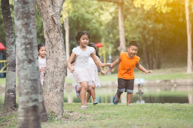 Asian children having fun to run and play together in the park in vintage color tone Premium Photo