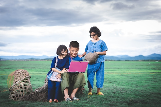 Asian children in local dress are using laptop for education and communication at countryside of thailand. Premium Photo