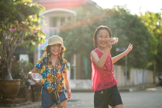 매우 더운 날씨에 친구에게 물 튀김 총을 사용하는 아시아 어린이, Songran 축제는 태국에서 매우 인기있는 축제입니다 프리미엄 사진