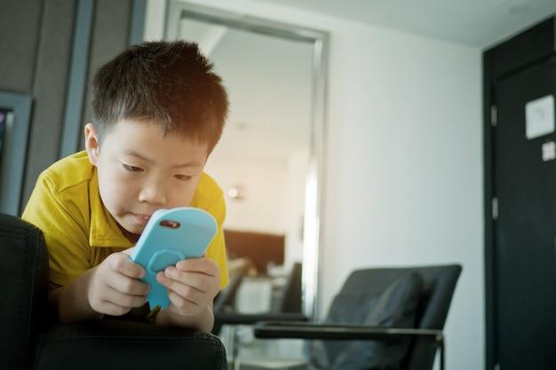 アジアの中国人の少年がベッドでスマートフォンをプレイ、子供が電話を使用してゲームをプレイ、中毒ゲームや漫画、 Premium写真