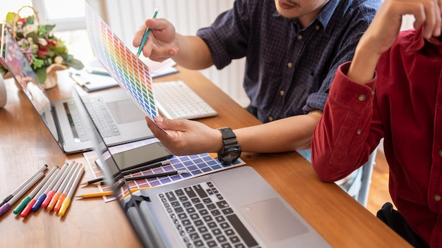 Азиатские коллеги дизайнер рисования эскизов на графическом ноутбуке. Premium Фотографии
