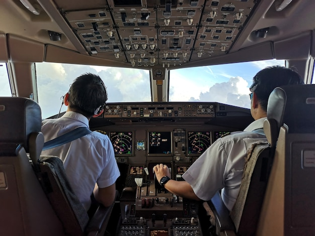 Asian commercial pilots in cockpit operating the airplane to avoid cloudy weather. Premium Photo