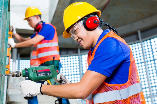 Asian construction workers drilling in building walls Premium Photo
