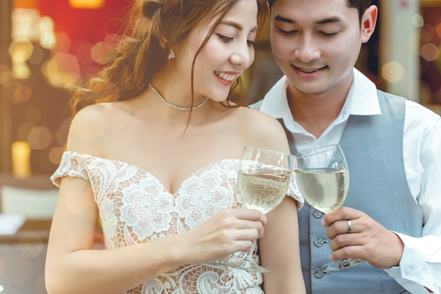 Asian couple cheer drinking together in restaurant. Premium Photo