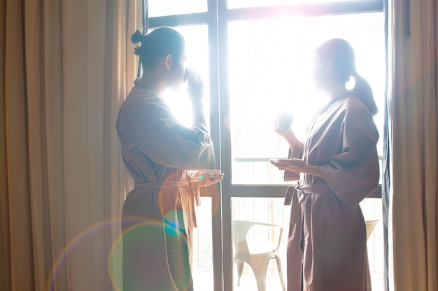 Asian couple drinking coffee and looking out of window. Premium Photo