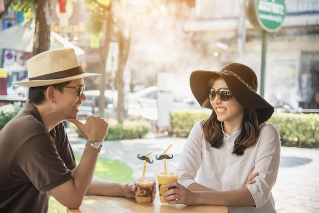 Asian couple enjoy traveling sitting at coffee shop Free Photo