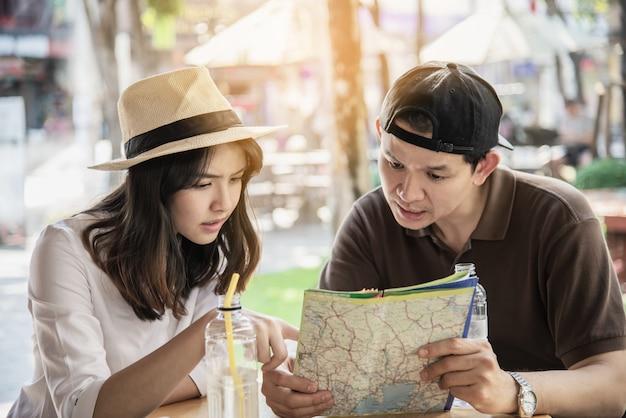 Asian couple enjoy traveling sitting at coffee shop Free Photo