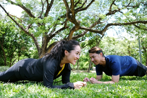 Premium Photo | Asian couple exercising and planking workout together on  grass field in the garden