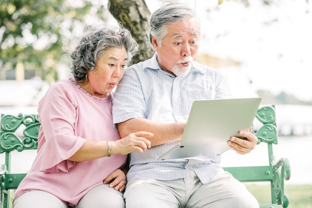 Asian couple feeling surprised using laptop Premium Photo