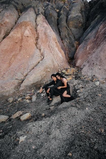 Азиатская пара в любви обнимает, сидя на скалах. любовная история Premium Фотографии