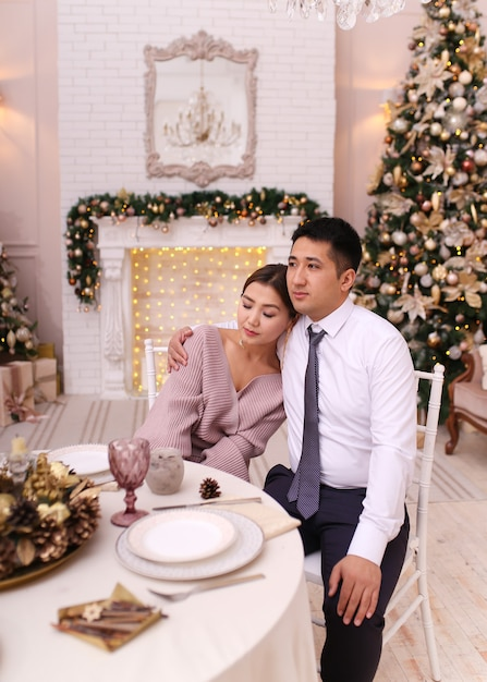 Азиатская влюбленная пара мужчина и женщина в элегантных нарядах обнимаются у камина и дерева, ужин Premium Фотографии