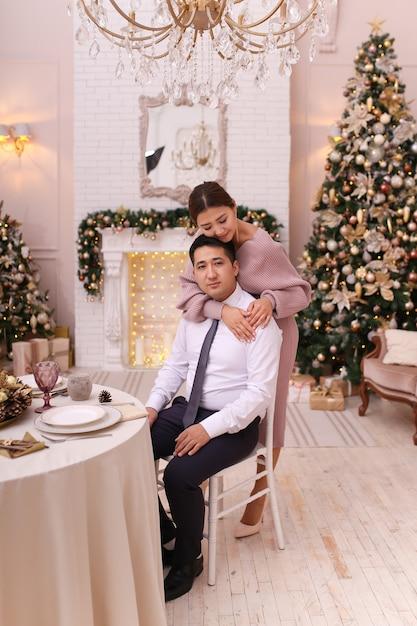 Азиатская влюбленная пара мужчина и женщина в элегантных нарядах обнимаются у камина и дерева Premium Фотографии