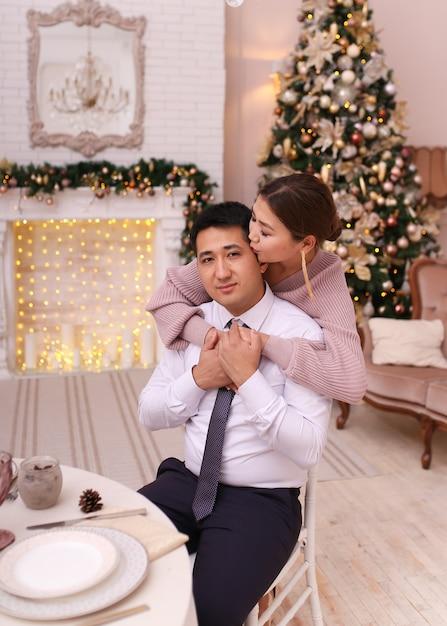 Азиатская влюбленная пара мужчина и женщина в элегантных нарядах сидят у камина и елки, рождественский ужин Premium Фотографии