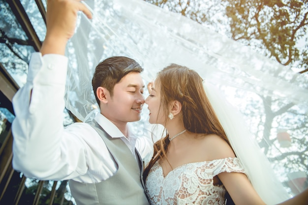 Asian couple kissing under the veil. Premium Photo
