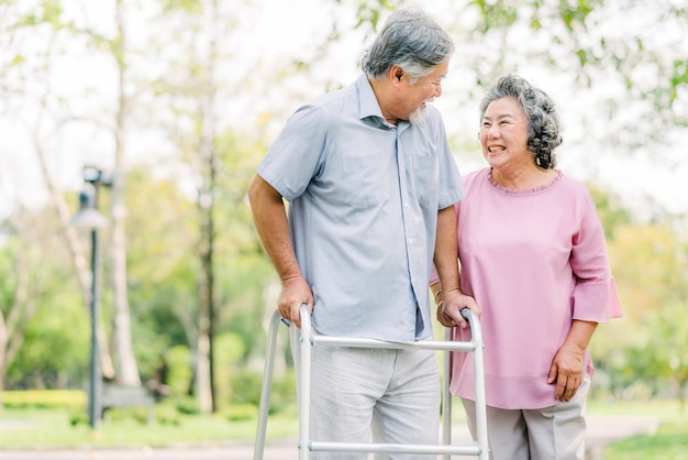 Asian couple laughing while walking with walker in the park Premium Photo