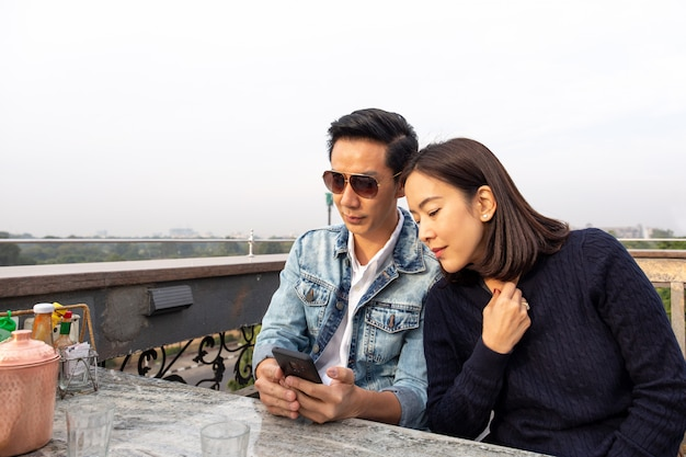 Asian couple looking at cellphone on outdoor cafe. Premium Photo