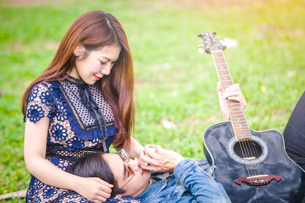 Asian couple in love playing acoustic song  guitar sitting on grass in the park Premium Photo