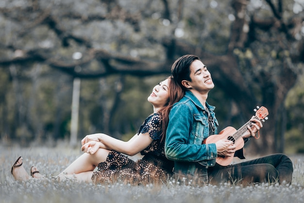 Asian couple in love playing acoustic ukulele song sitting