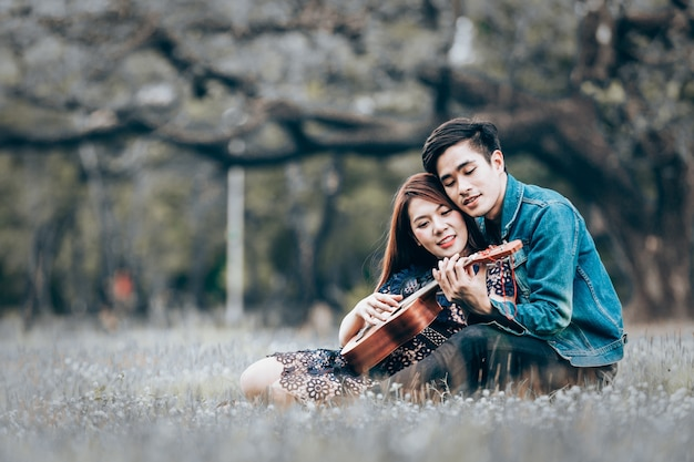 Asian couple in love playing acoustic ukulele song sitting on grass in the park Premium Photo