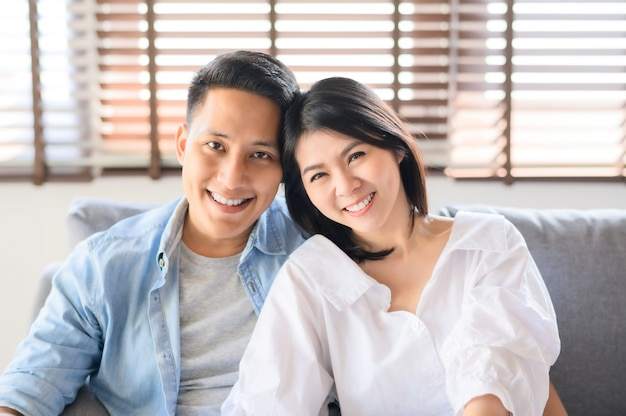 Asian couple in love smiling relaxing on sofa at home Premium Photo