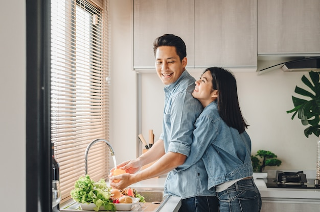 Asian couple lovers hug in the kitchen while cooking at home Premium Photo