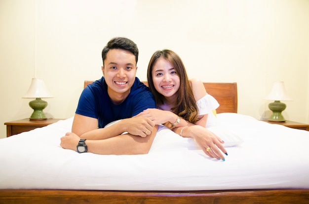 Asian couple lying on bed, holding hand together Premium Photo