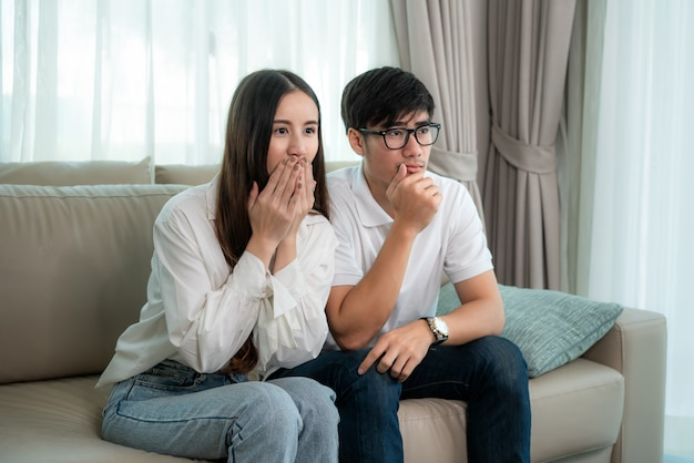 Asian couple man and woman watching and enjoying terror tv movie sitting on a couch together in the livingroom at home. family lifestyle relax and recreation concept. Premium Photo