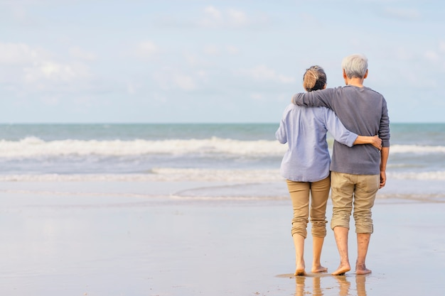 Asian couple senior walking on the beach holding hands.honeymoon family together happiness lifestyle.life after retirement.plan life insurance Premium Photo