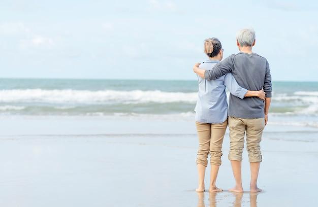 手を繋いでいるビーチの上を歩くアジアカップルシニア。新婚旅行家族一緒に幸せなライフスタイル。退職後の生活。生命保険を計画します。 Premium写真